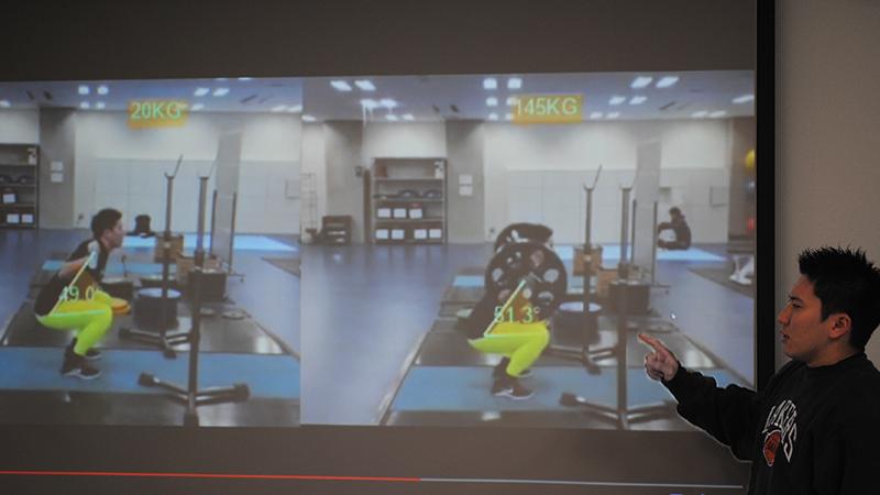 ダートフィッシュのウエイトリフティングの分析映像。20kgと145kgのバーベルを持ち上げる際のフォームを撮影し、2画面で比較。体幹や膝の角度を表示している様子。